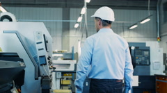 Engineer is Setting Up CNC Lathe Machine on Factory Stock Footage