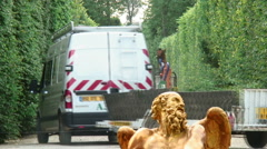 Van and trailer with branches between hedges in a garden with a statue. Stock Footage