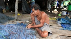 Old Thai man working with a fishing net in a fishing village . Thailand Stock Footage