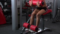 Woman doing sitting curls in a gym weight room. Stock Footage