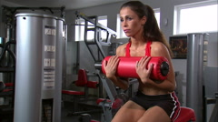 Woman doing sitting curls in a gym. Stock Footage