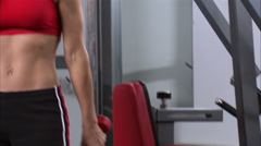 Woman doing arm curls with a pair of dumbbells in a weight room. Stock Footage