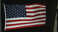 The American flag waving in the wind with black background. Stock Footage