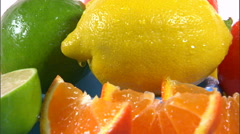 Stock Video Footage of Close shot of assorted citrus fruit rotating on a white screen.