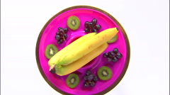 Assortment of fruit on a rotating purple plate. - stock footage