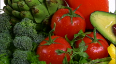 Stock Video Footage of Assortment of vegetables rotating on a white screen.