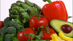 Zoom out shot of an assortment of vegetables rotating on a white screen. - stock footage
