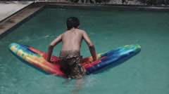 Boy playing in swimming pool Stock Footage