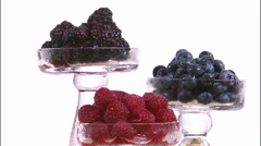 Rotating glass cups of berries on a white screen. Stock Footage