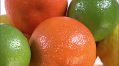 Close shot of varied fruit rotating on a white screen. - stock footage