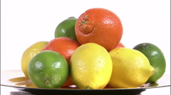 Assorted citrus fruits on a spinning plate on a white screen Stock Footage