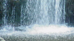 Water from a waterfall splashing into a pond. - stock footage