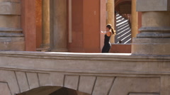 Woman jogging and pausing to stretch in a Italian architecture arcade. - stock footage