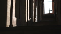 Shot up steps in an architecturial arcade with a cross visible. Stock Footage