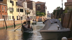 Tourists in a gondola on a canal in Venice, Italy. Stock Footage