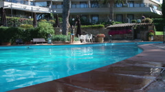 Woman diving in a swimming pool at resort. - stock footage