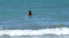 A woman walking into the waves at the beach in Italy. Stock Footage