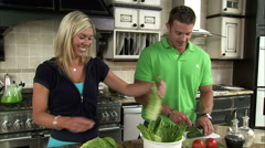 Couple preparing a salad in a kitchen. Stock Footage