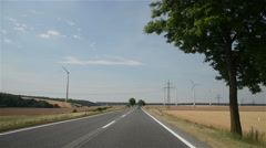 Rural road across the field to wind power Stock Footage