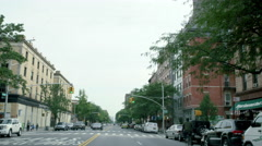 Man on bicycle bicycling down Frederick Douglas Blvd in Harlem, NYC Stock Footage