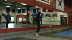 Male martial artist doing a spin kick in studio Stock Footage