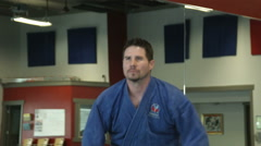 Man in karate studio practicing nunchuck weapon moves Stock Footage