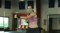 Female in a gym doing punch and kick combinations - stock footage