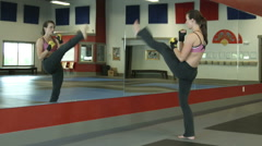 Female in a gym doing kick warmups in the mirror - stock footage