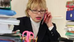 Senior woman chief accountant in glasses and with red smartphone Stock Footage