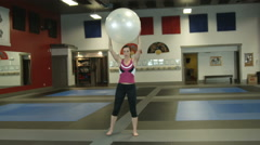 Girl in a gym working out with fitness ball Stock Footage