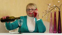 Woman sits at the table, drinks red wine and speaks on smartphone Stock Footage