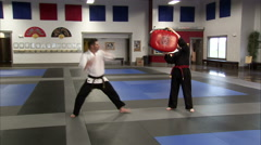 Man kicking a bag held in the air at a karate studio. - stock footage