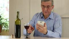 Man with smartphone drinking wine Stock Footage