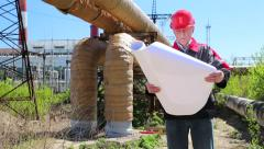 Maintenance engineer with project drawing at heat electropower station - stock footage
