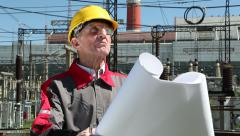 Planner with project drawing at heat electropower station - stock footage