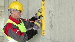 Worker in yellow hard hat with level at building site Stock Footage