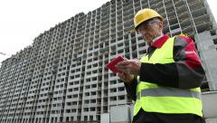 Master builder with red smartphone at construction site Stock Footage