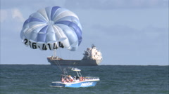 Parasail boat in the ocean with cargo ship in the background. Stock Footage