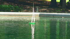 Toy boat sailing on a pond. Stock Footage