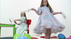 Royalty Free Stock Footage of Young twins, one spinning, one applying makeup. Stock Footage