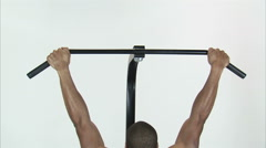 Back of a man doing pull-ups on a white Stock Footage