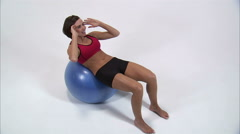 Royalty Free Stock Footage of Woman doing sit-ups on an exercise ball on a white Stock Footage