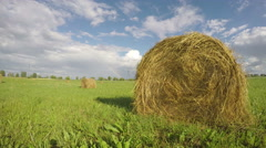 Stock Video Footage of landscape with hay bales on summer field and rainbow. Timelapse 4K
