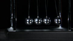 Stock Video Footage of Newton's Cradle balls colliding on black background.