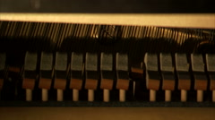 Piano hammers striking strings of a piano. Arkistovideo