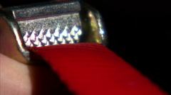 Close up of a red strap going through a cam clamp. Stock Footage
