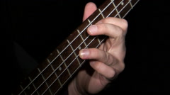 Neck of a bass guitar being played against a black background. Stock Footage