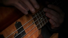 Hands playing a bass guitar on a black background. Stock Footage