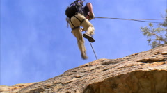 Shot of a mountain climber rappelling down a cliff. - stock footage