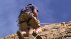 Shot of a rock climber climbing up a cliff. Stock Footage